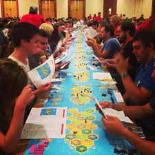 One very long game board of the Settlers of Catan board game stretching across many tables, as hundreds of people sit along it playing the game with each other in small groups. The ultimate in social gaming?