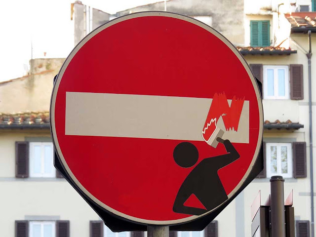 Painting the bar on a no-entry sign, Clet Abraham, Florence