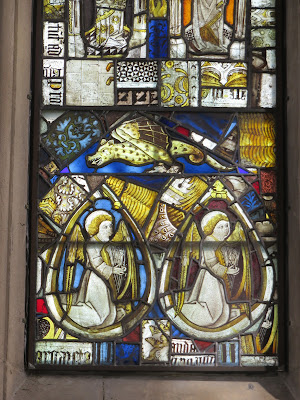 Medieval stained glass including angels and a dragon