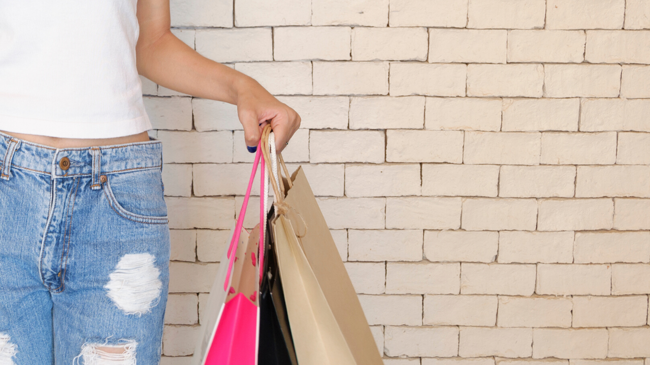 mid shot of a woman whith blue jeans and white top holding shopping bags