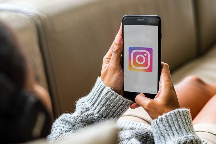 Mulher segurando celular com Instagram