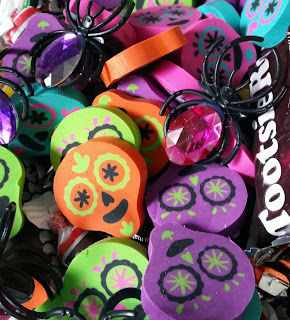 A jumple of orange, yellow, purple, green and black skull erasers and a couple spider rings with big, fake jewels on them. There's also a Tootsie Roll candy on the right side of the picture.