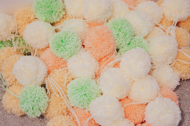 Multi-coloured pom-poms in a pile