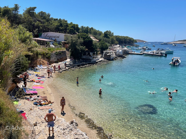 People on a pebbly beach by the sea in Croatia's Pakleni Islands