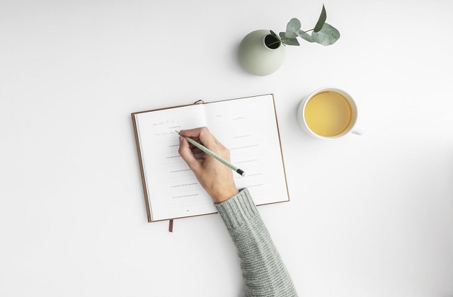 a woman's hand writing on a diary on the table with juice and plant