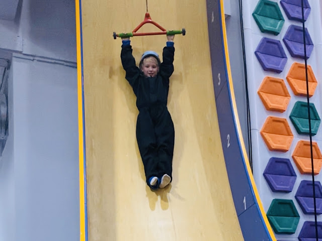 A girl in a helmet and black boiler suit holding on to a bar which is pulling her vertically up a slide