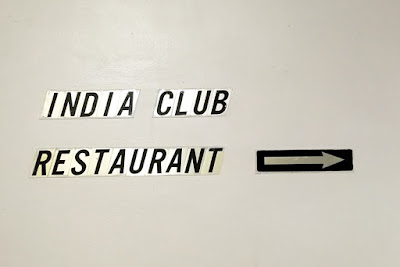 Individual black letters on pale gold backgrounds are stuck onto a cream wall. They say INDIA CLUB RESTAURANT and to their right is stuck a gold arrow on a black background,  pointing right.