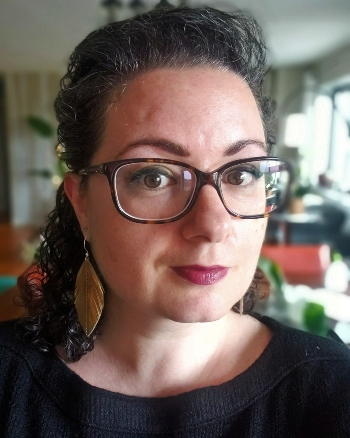 Olga Berman wearing glasses and leather feather earrings.