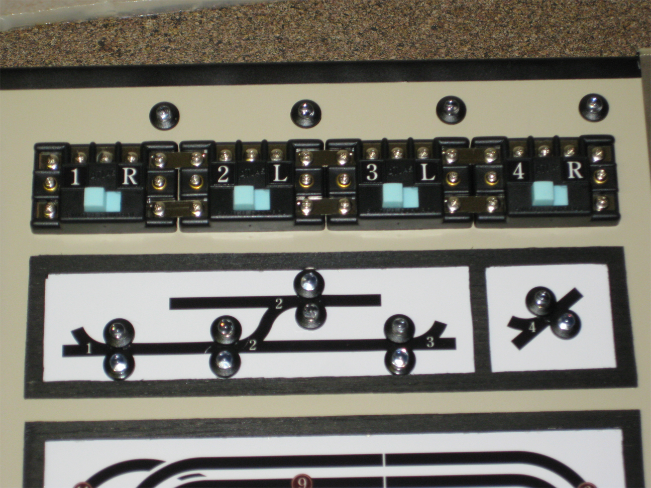 Control panel with Atlas switches and homemade letter labels installed along with turnout position LED indicator lights