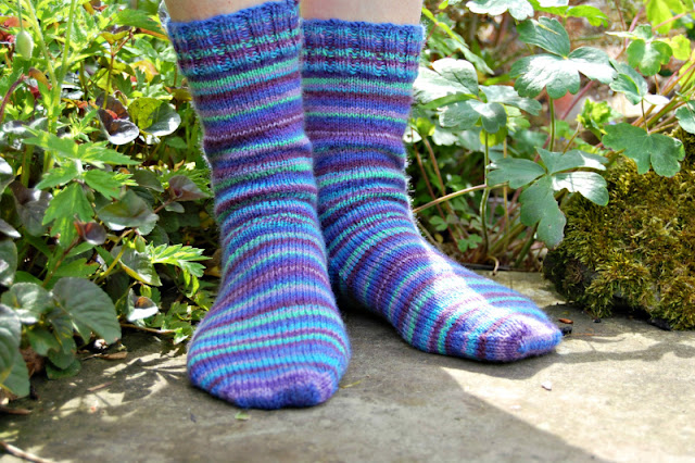 A pair of blue and multi-coloured striped socks being modelled on feet.  Winwick Mum is standing on a stone flag in the sunshine with plants around her