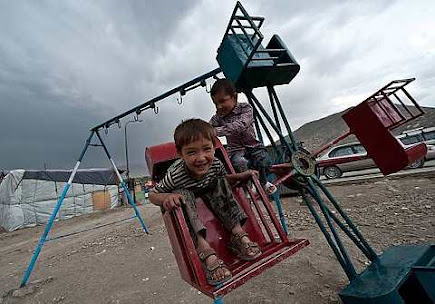 Afghan children play on swings in Kabul