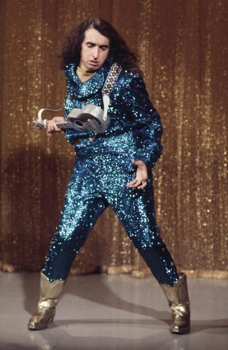 Tiny Tim on stage with ukulele, wearing sparkly blue jumpsuit and gold cowboy boots