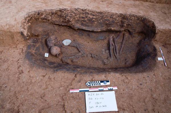 Bestattungen im Nildelta. Zu sehen ist ein Skelett auf der Seite liegend mit einem Tontopf.