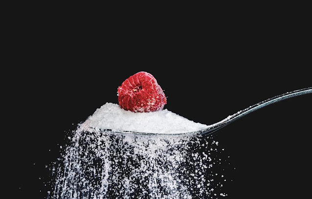 A raspberry carefully placed on a spoon full of sugar.