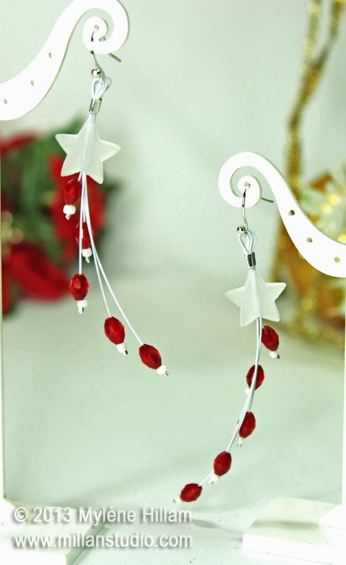 Star of Bethlehem Earrings featuring a white star with strands of curved white beading wire with a red oval crystal on each tip.