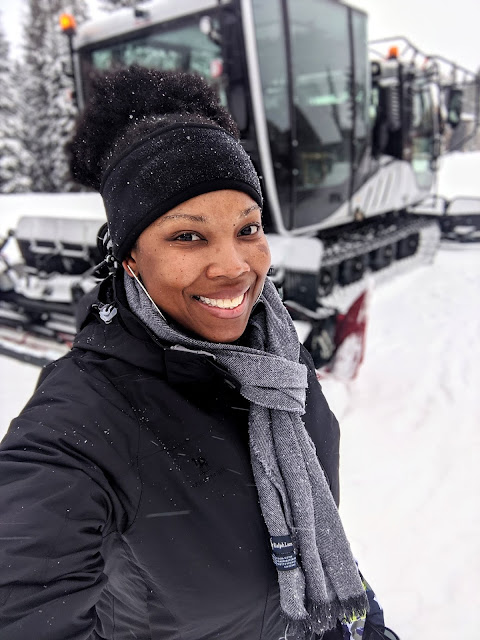 Young black woman standing in front of snowcat in Breckenridge