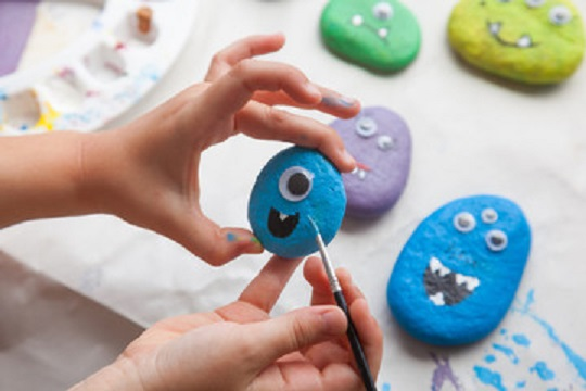 Child painting stones and turning them into monsters with googly eyes