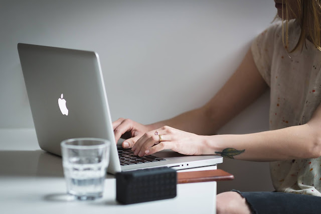 person typing on a Macbooks