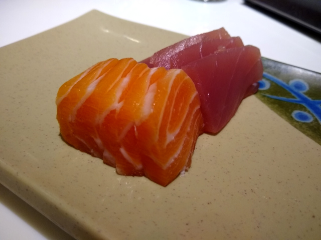 Some slices of raw salmon and tuna (sashimi) inside a beige plate.