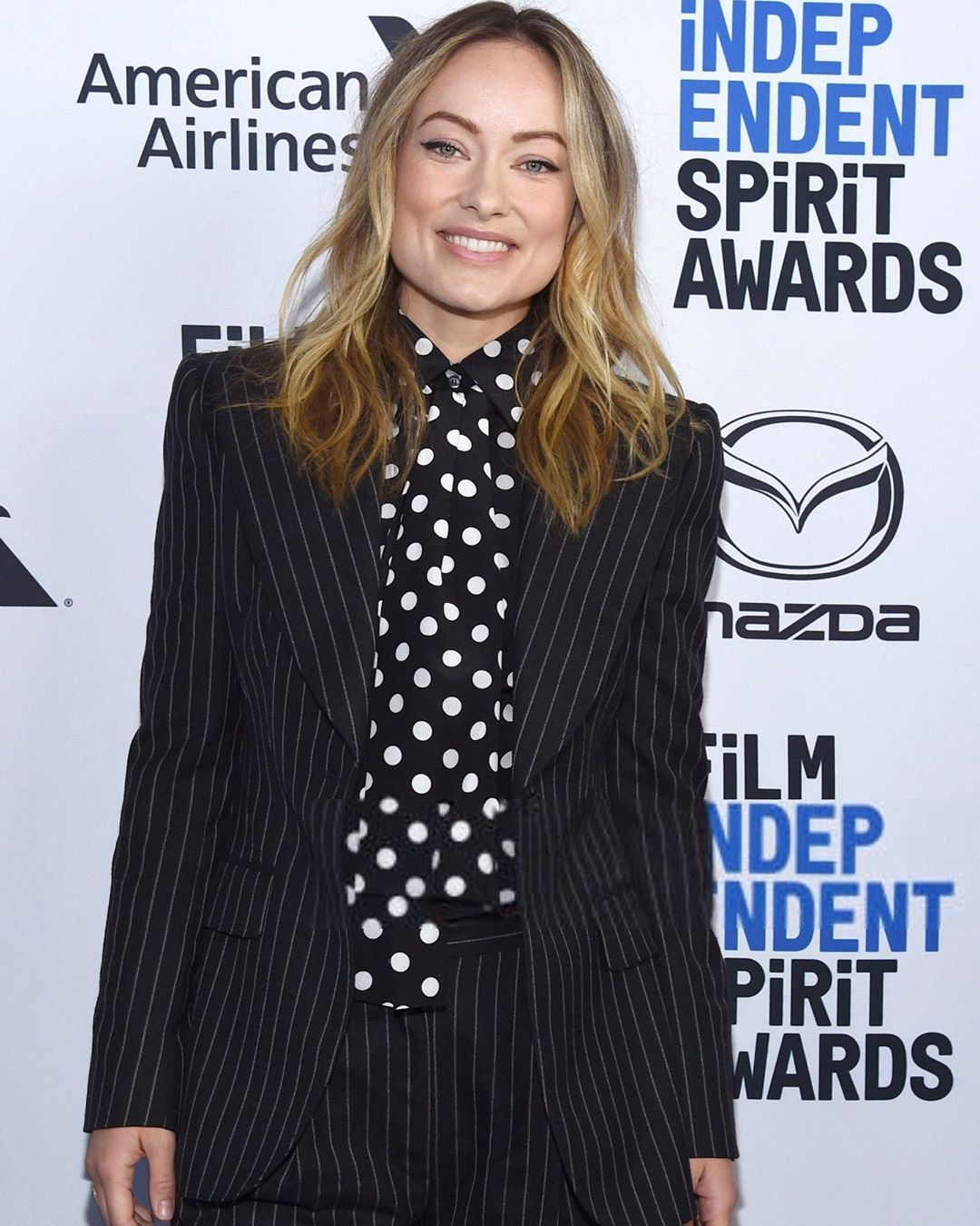 Olivia Wilde wows in pinstripe suit and white polka dot shirt and tie at FI Spirit Awards Brunch