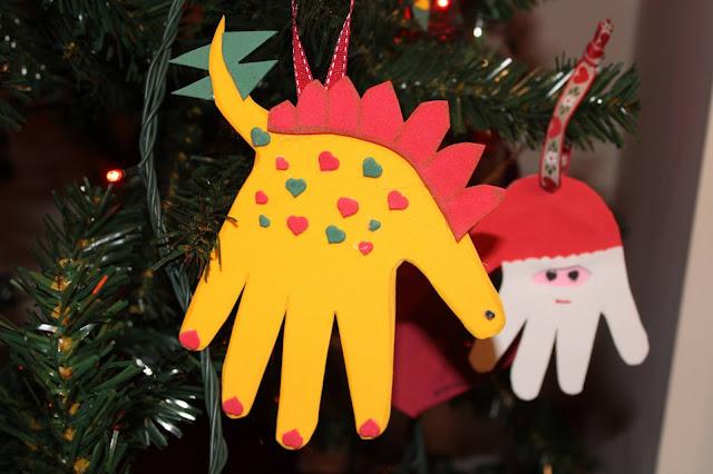 ornamento de Natal, usando o molde de uma mão, em formato de stegossauro