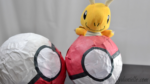Paper Mache Pokeball with a stuffed Pokemon peeking out.