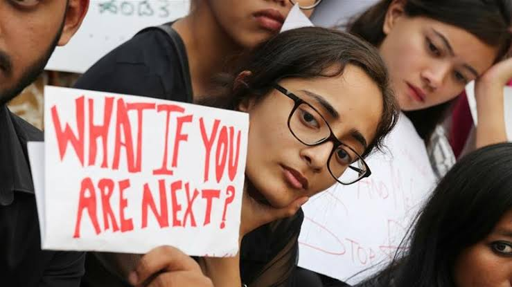 Girl holding a slogan saying what if you are next with teary eyes.