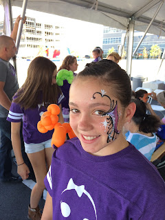 A Young girl with a balloon monkey on her shoulder and a pretty face paint design