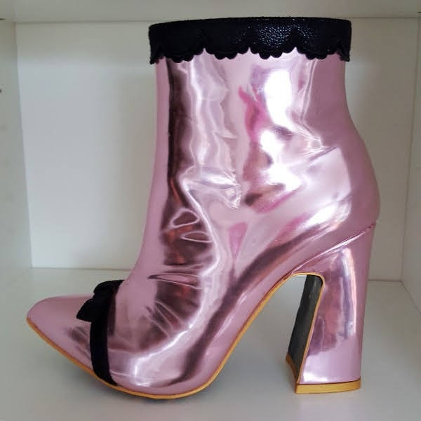 pink mirrored metallic ankle boot with black trim on shelf
