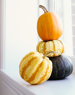 stack of pumkins on window sill