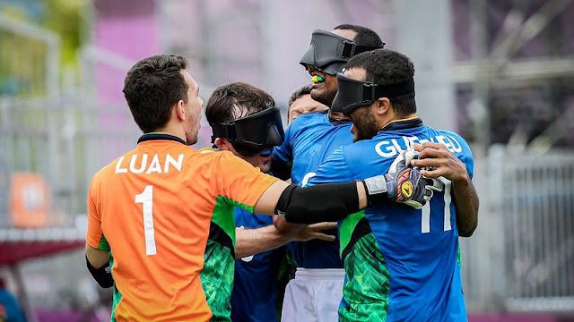 Jogadores da seleção brasileira de futebol de 5, de uniforme azul, se abraçam; eles têm tampões pretos; o goleiro, de costas, está de laranja