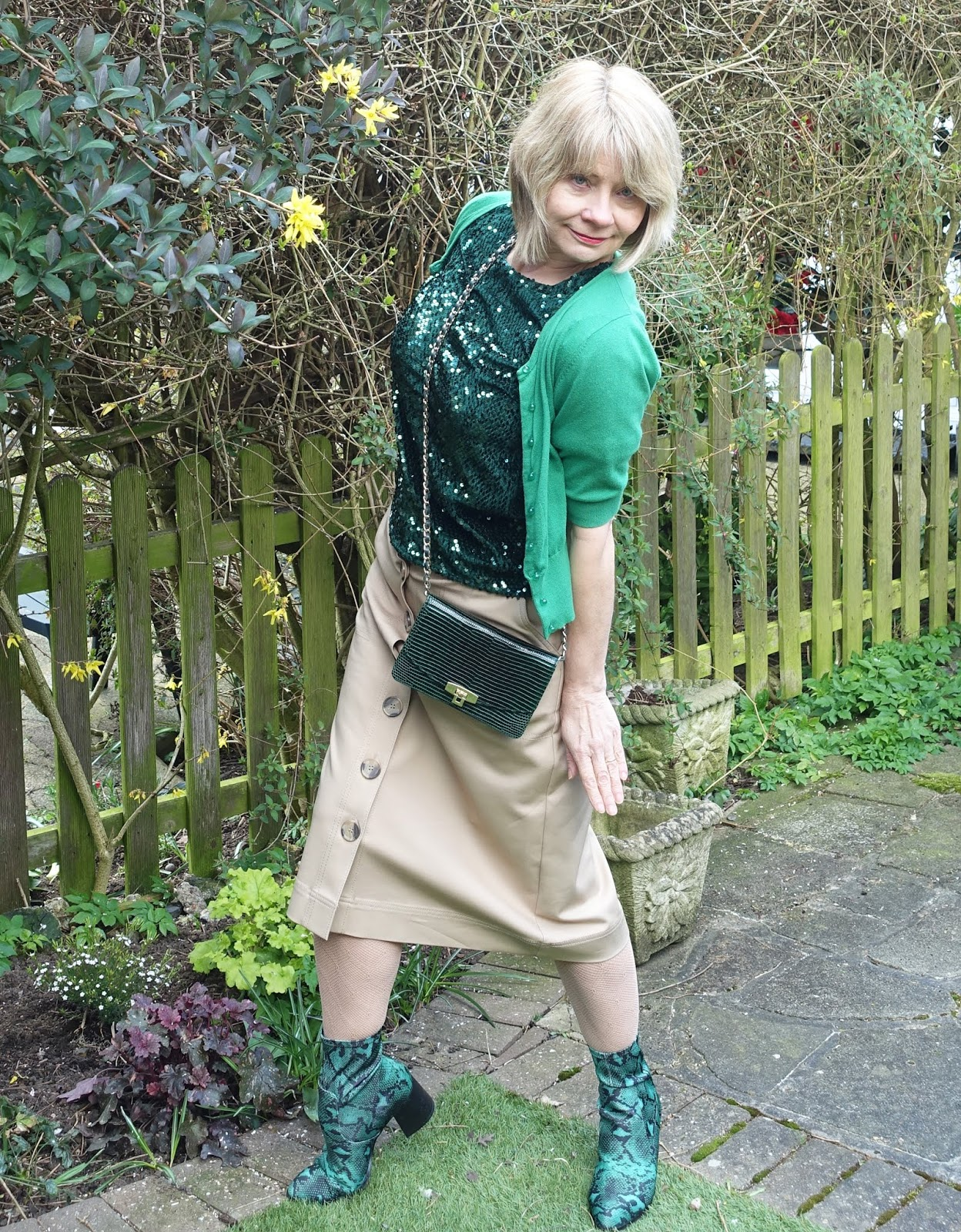 Add a fun twist to a neutral beige midi skirt with snakeskin boots, a cross-tre-body bag and green snakeskin boots