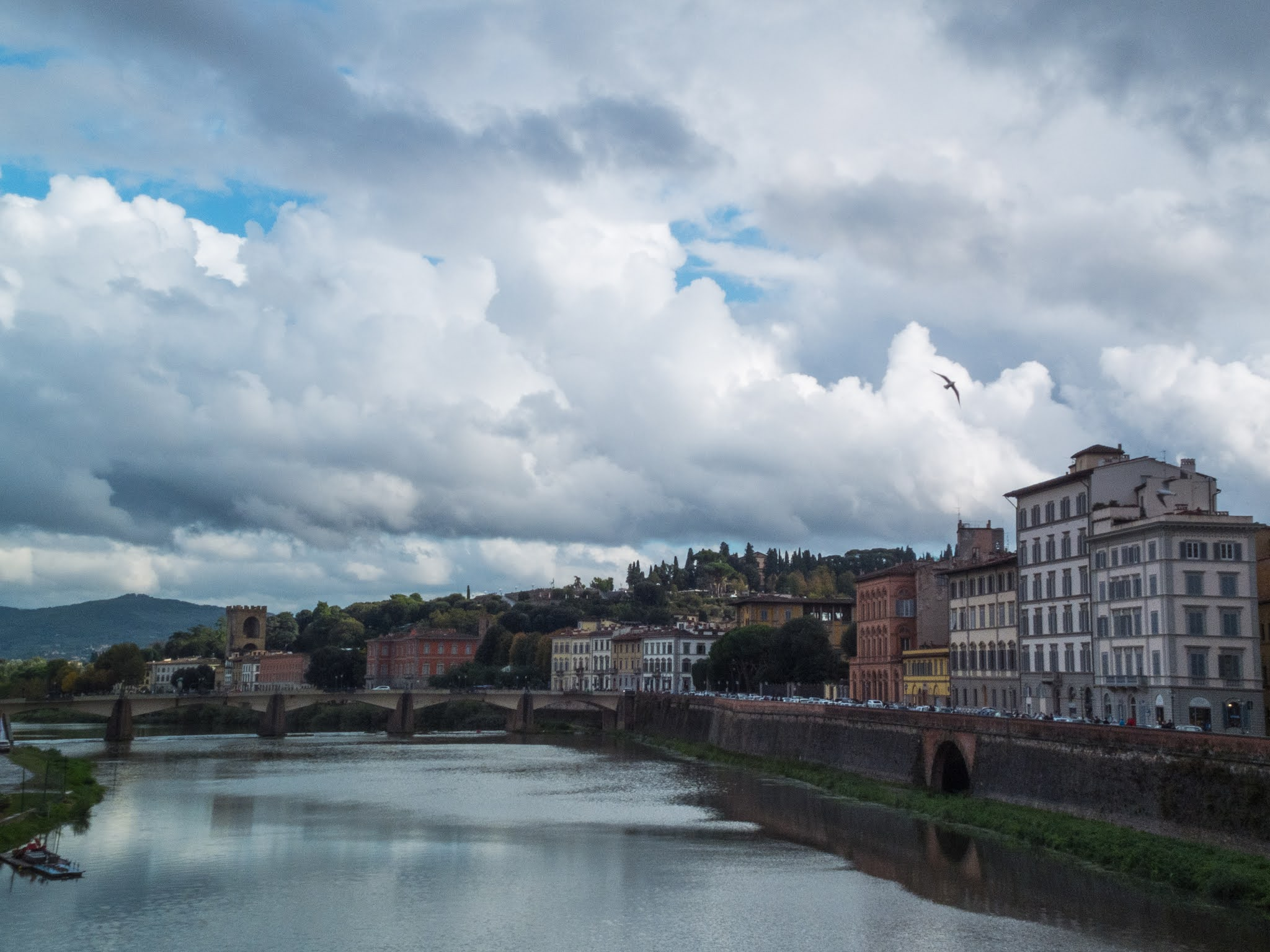 Ponte alle Grazie over the Arno river in Florence on a cloudy day.