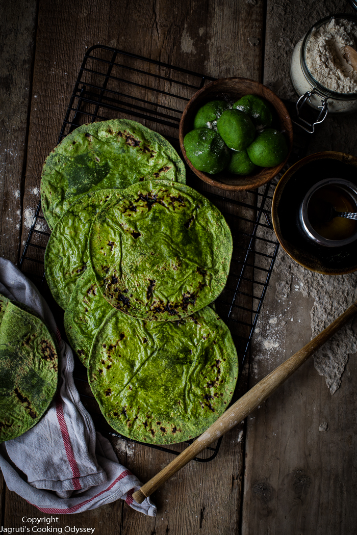 Induan style spinach flatbreads are applied with ghee and laid on a white kitchen tea towel.