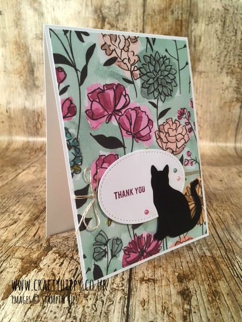 This image depicts a handmade card with a floral background and a black cat, with the sentiment Thank You which has been created using the Cat Punch, Share What You Love Specialty DSP and Thoughtful Banners by Stampin' Up!