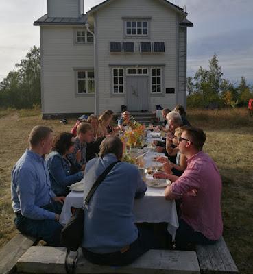 Pitkä pöytä ulkona tutkimusaseman edessä, jonka ääressä noin pari kymmentä ihmistä kesällä.