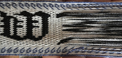 A photo of a section of tablet woven band with the weft removed for part of it