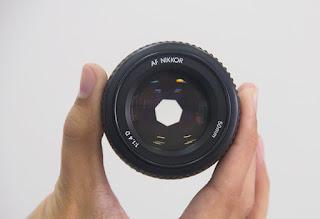Mãos Segurando uma Lente de Câmera