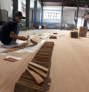 pemasangan lantai kayu di sarana olahraga basket