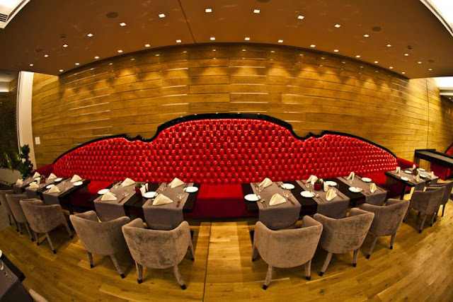 Picture of many square dining tables lined up by the huge long sofa with red leather on the wooden wall