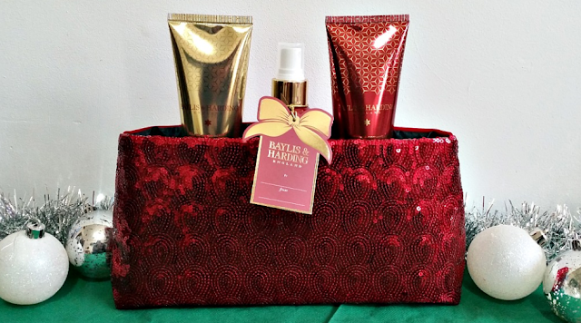 A red clutch bag holding some baylis and harding products