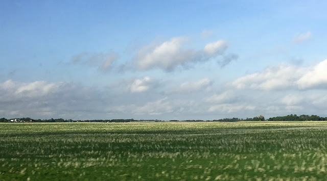 image of alberta prairie field with cloudy blue sky