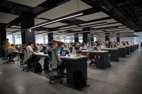 escritório com diversas mesas e funcionários
