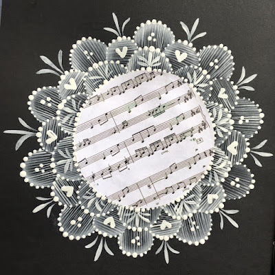 A circle of music paper framed by hand painted lace like designs from You Can Folk it