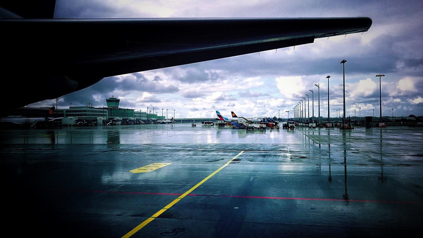 Münchner Flughafen Gebäude bei Regen man sieht Flugzeuge