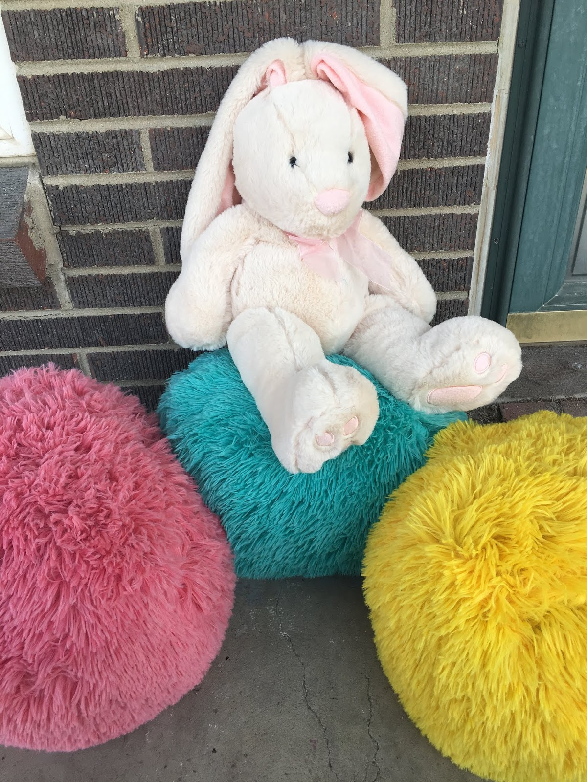a bunny stuffed animal sits on top of bright color pillows