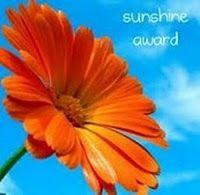 Premio rayo de sol. Flor anaranjada con cielo de fondo y mensaje que dice sunshine award