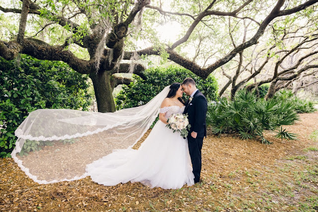 bride and groom smiling with veil blowing in the wind