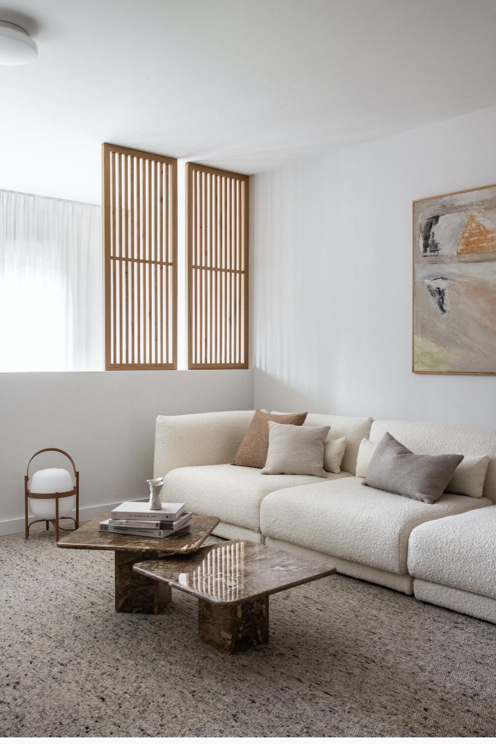 Un grand canapé en laine bouclée devant un claustra culissant en bois. Murs blanc, tapis beige, tables basses gigognes carrées.