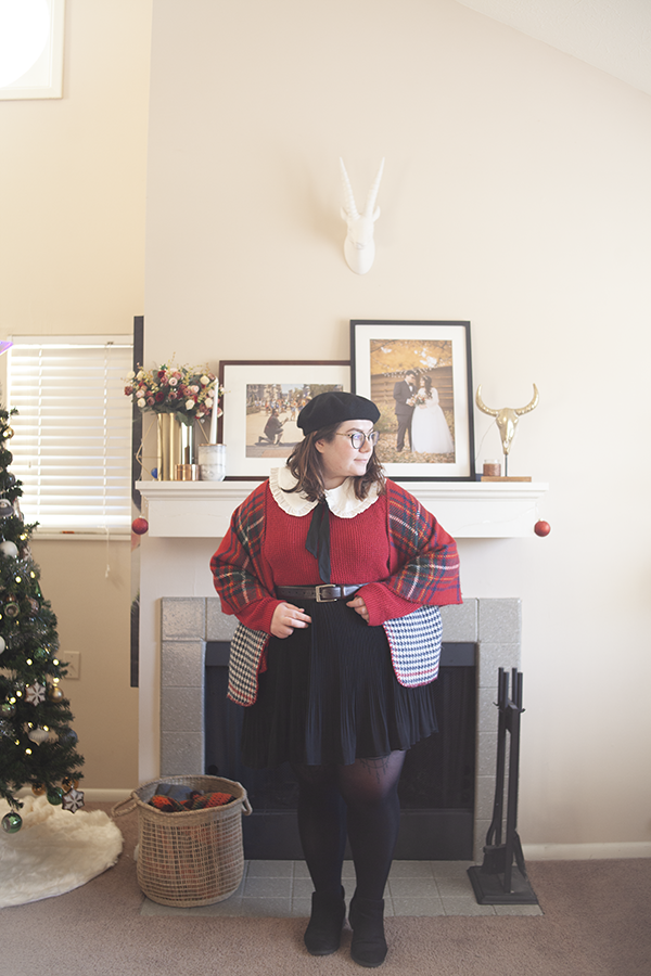 An outfit consisting of a black beret, a white frilled Peter Pan collar under a red sweater, tucked into a black pleated knee length skirt, black ankle boots, and a red plaid shawl over top.